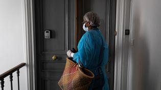 Une aide à domicile rapporte les courses à une personne âgée dont elle prend soin (photo d'illustration). (ALEXIS SCIARD / MAXPPP)