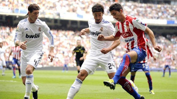 Le joueur de Gijon Daniel Carrico face aux joueurs du Real