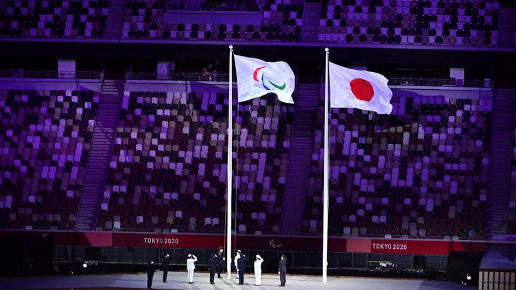 Le drapeau paralympique est hissé à côté de celui du Japon lors de la cérémonie d'ouverture des Jeux paralympiques de Tokyo, le 24 août 2021. (CHARLY TRIBALLEAU / AFP)
