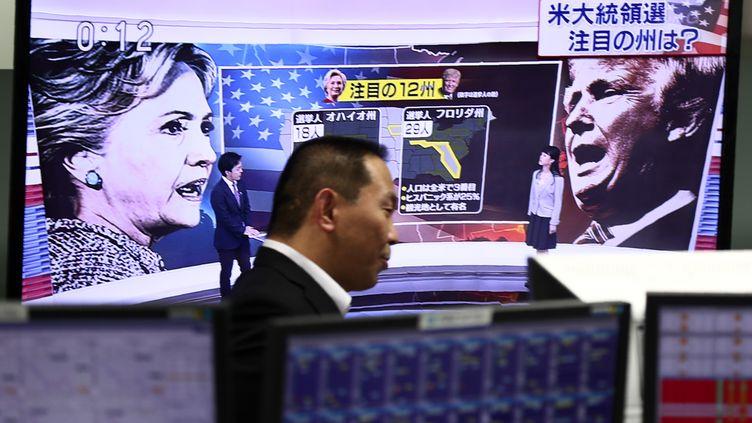 Un employé de la Bourse japonaise regarde la soirée électorale américaine, le 9 novembre 2016, à Tokyo (Japon). (BEHROUZ MEHRI / AFP)