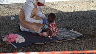 Un membre des équipes médicales soigne un enfant atteint de l'épidémie Ebola, au centre de traitement de Kenama, au Sierra Leone, le 15 noivembre 2014. (FRANCISCO LEONG / AFP)