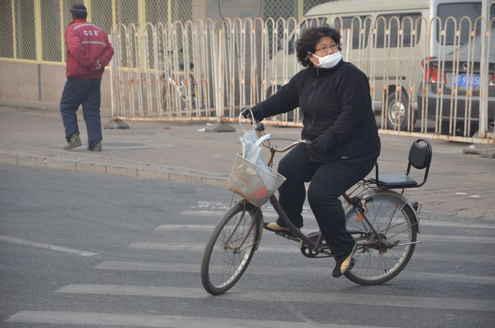 Ce type de masque, en coton, que porte cette cycliste à Pékin en janvier 2014, ne protège absolument pas des particules fines PM2.5. (THOMAS BAIETTO / FRANCETV INFO)