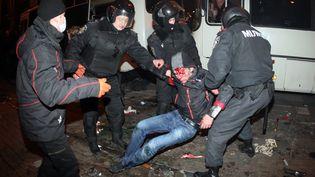 Des policiers relèvent un homme blessé lors d'affrontements à Donetsk (Ukraine), le 13 mars 2014. (ALEXANDER KHUDOTEPLY / AFP)