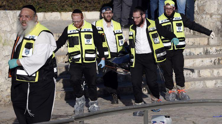Des secouristes emportant les restes d'un des Palestiniens qui a tué une policière à Jérusalem (Israël), avant d'être abattu, le 3 février 2016. (AHMAD GHARABLI / AFP)