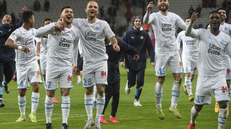 Les joueurs de l'Olympique de Marseille célèbrent leur victoireà Lille, le 16 février 2020. (FRANCOIS LO PRESTI / AFP)