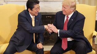 Le président américain Donald Trump (à droite) serre vigoureusement la main au Premier ministre japonais Shinzo Abe, à la Maison Blanche, le 10 février 2017. (CHIP SOMODEVILLA / DPA / AFP)