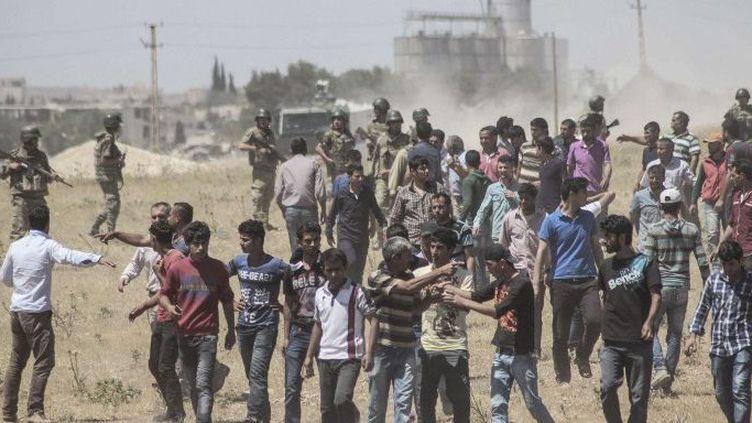 Dans la province de Sanliufa, des soldats turcs empêchent des Kurdes de traverser la frontière syrienne pour contrer la nouvelle offensive de Daech contre Kobané, le 25 juin 2015. (Halil Fidan/Anadolu Agency)