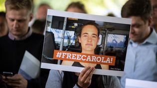 """Une manifestante porte une affiche """"Libérez Carola"""", lors d'un rassemblement à Cologne (Allemagne), mardi 2 juillet 2019. (FEDERICO GAMBARINI / DPA / AFP)"""
