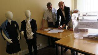 Le maire LR de Provins (Seine-et-Marne), Olivier Lavenka (au centre), signe le PV de la consultation pour le port de l'uniforme. (MAXPPP)