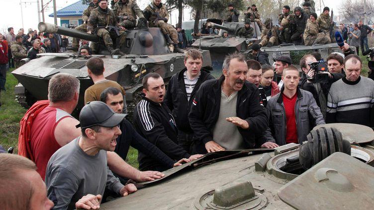 Des manifestants pro-russes bloquent l'avancée d'une colonne de chars ukrainiens, le 15 avril 2014 à Kramatorsk (Ukraine). (ANATOLIY STEPANOV / AFP)