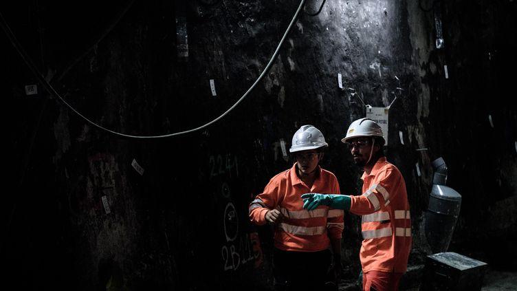 Deux personnes travaillent dans un tunnel de métro à la station Saint-Michel, à Paris, le 29 juin 2016, pendant les travaux de rénovation du RER C. (PHILIPPE LOPEZ / AFP)