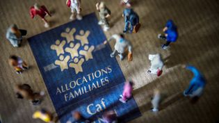 Figurines are displayed around the logo of the Caisse d'allocations familiales (Family Allocations Office, or CAF) on October 8, 2014 in Lille, northern France. Members of parliament of France's ruling Socalist Party (PS) consider to modulate family allowances according to their earnings. AFP PHOTO / PHILIPPE HUGUEN (PHILIPPE HUGUEN / AFP)