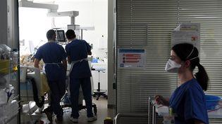Des soignants prennent en charge un malade du Covid-19 dans le service de soins intensifs de l'hôpital Ambroise Paré deBoulogne-Billancourt (Hauts-de-Seine), en mars 2021. (ALAIN JOCARD / AFP)