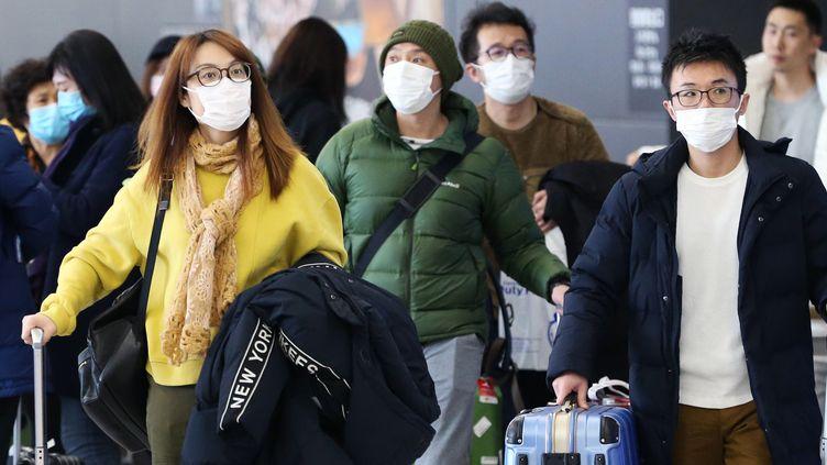 Des voyageurs portent des masques à l'aéroport international du Chubu, à Nagoya (Japon), le 24 janvier 2020. (SATOSHI OGA / YOMIURI)