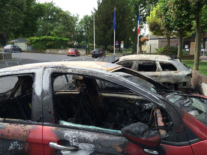 Des voitures brûlées sur la place devant la mairie à Beaumont-sur-Oise (Val-d'Oise), jeudi 21 juillet 2016. (CLEMENT PARROT / FRANCETV INFO)