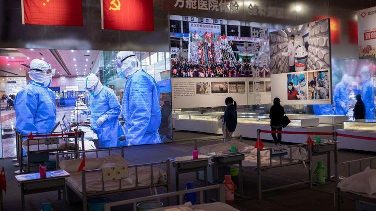 Des visiteurs prennent part à une exposition mettant en scène la gestion de l'épidémie de Covid-19 à Wuhan (Chine),dans l'un des anciens hôpitaux de fortune construits pendant la crise sanitaire, le 15 janvier 2021. (NICOLAS ASFOURI / AFP)