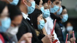 Des Chinois avec des masques en février 2020. (ANTHONY WALLACE / AFP)