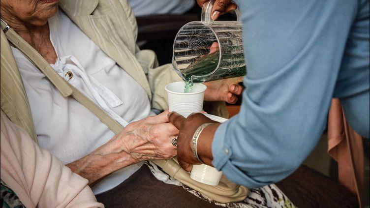 Une personne âgée reçoit un verre de sirop et d'eau, dans un EHPAD à Paris, lors de l'épisode de canicule qui sévit en France, le 25 juin 2019. (LUC NOBOUT / MAXPPP)