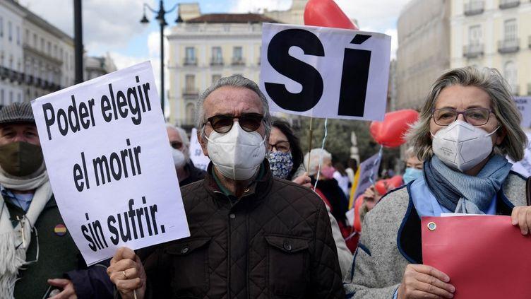 """Un homme tient une pancarte où l'on peut lire """"Choisir de mourir sans souffrir"""", lors d'une manifestation des pro-euthanasie, à Madrid (Espagne), le 18 mars 2021. (JAVIER SORIANO / AFP)"""