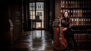 Le violoncelliste Camille Thomas joue dans la bibliiothèque de l'Insttitut de France à Paris. (MARTIN BUREAU / AFP)
