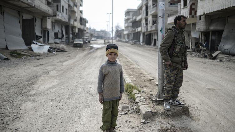Un petit garçon syrien au milieu des débris, dans la ville de Kobani (Syrie), le 28 janvier 2015. (BULENT KILIC / AFP)