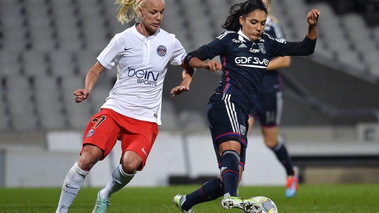 Louisa Necib (OL) à la lutte avec Caroline Seger (PSG) lors du seizième de finale de la Ligue des Champions 2014-2015 entre Paris et Lyon. (JEFF PACHOUD / AFP)