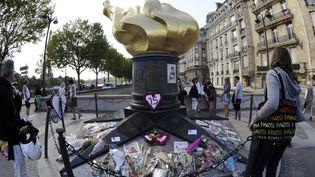 Le 31 août 2012, des gens rendent hommage à Lady Diana à côté du tunnel du pont de l'Alma, à Paris, où la princesse a trouvé la mort, le 31 août 1997. (BERTRAND GUAY / AFP)