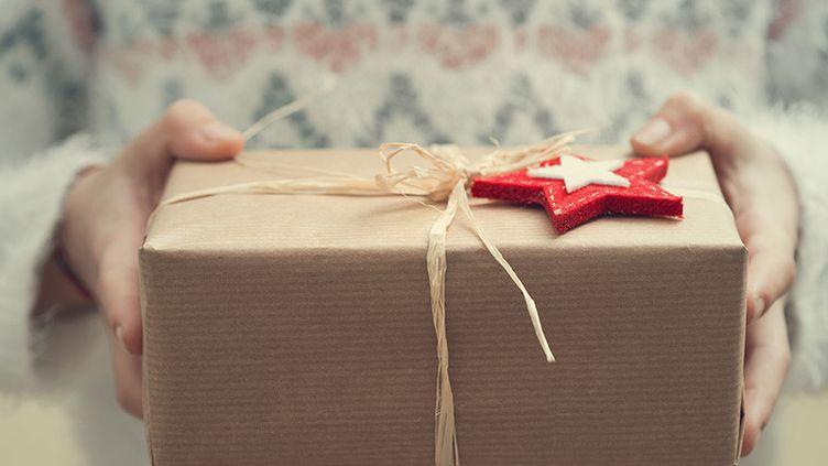 Une personne offre un cadeau pour Noël (illustration). (FRANCESCO CARTA FOTOGRAFO / GETTY IMAGES)