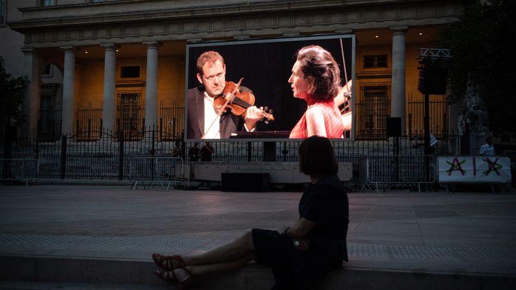 Une femme regarde un concert dirigé parThomas Hengelbrock, sur la place de Verdun, à Aix-en-Provence. Une partie de l'édition 2020 du festival a été annulée à cause de la pandémie. (CLEMENT MAHOUDEAU / AFP)