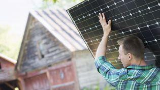 Un homme installe un panneau solaire. (TIM ROBBINS / MINT IMAGES / AFP)