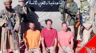 Des jihadistes d'Al-Qaïda au Maghreb islamique encadrent trois otages européens sur cette photo diffusée le 9 décembre 2011. (AGENCE NOUAKCHOTT INFORMATIONS / AFP)