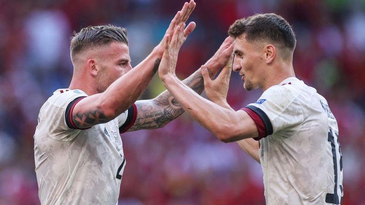 Toby Alderweireld et Thomas Meunier célèbrent la victoire de la Belgique après le match de footballface au Danemark, à Copenhague, le 17 juin 2021. (VLADIMIR PESNYA / AFP)