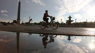 Une cycliste circule place de la Concorde le 22 juin 2015 à Paris. (LUDOVIC MARIN / AFP)