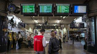 Un employer de la SNCF renseigne un voyagueur à la gare de Lyon Part Dieu en juin 2014. (Illustration) (JEFF PACHOUD / AFP)