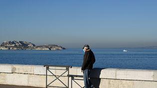 Un homme masqué marche le long de la corniche du Président-John-Fitzgerald-Kennedy, à Marseille (Bouches-du-Rhône), le 19 janvier 2021. (NICOLAS TUCAT / AFP)