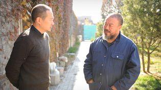 Ai Weiwei discute avec un ami devant son studio pékinois, le 9 novembre 2011. (PETER PARKS / AFP)