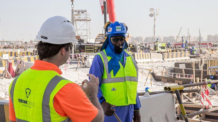 """Une photo, diffusée le 30 août 2018 par les organisateurs du Mondial de foot 2022, montre un ouvrier portant un """"gilet de refroidissement"""" sur un chantier à Doha(Qatar). (MOHAMED YOUSUF DABBOUS / QATAR WORLD CUP ORGANISERS / AFP PHOTO)"""