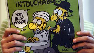 """Un homme regarde les caricatures du prophète Mahomet parues dans le numéro de """"Charlie Hebdo"""" daté du 19 septembre 2012, à Paris. (THOMAS COEX / AFP)"""