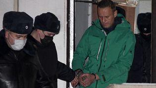 L'opposant Alexeï Navalny est escorté à la sortie d'un poste de police àKhimki (Russie), le 18 janvier 2021. (ALEXANDER NEMENOV / AFP)
