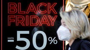 Une femme passe devant un magasin qui annonce des promotions pour le Black Friday. (ANA ESCOBAR / MAXPPP)