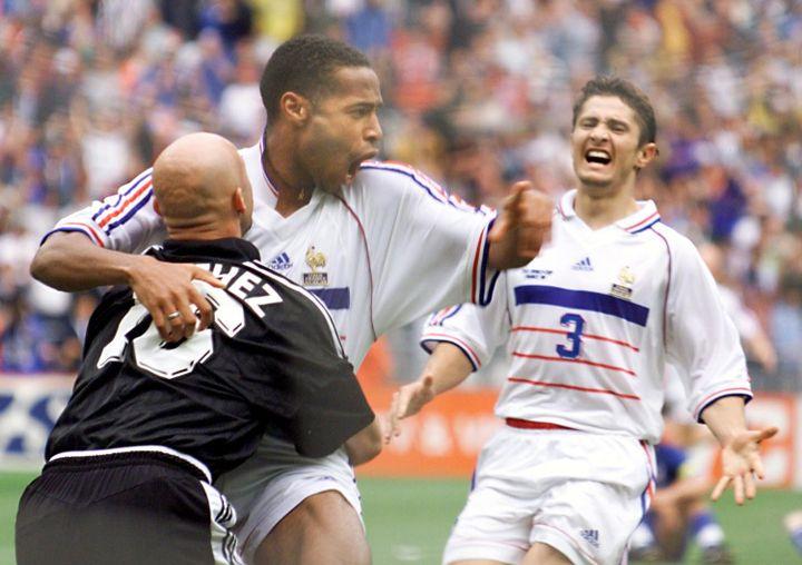 Thierry Henry se jette dans les bras de Fabien Barthez, sous les yeux deBixente Lizarazu, après la victoire de la France sur l'Italie, le 3 juillet 1998, à Saint-Denis. (GABRIEL BOUYS / AFP)