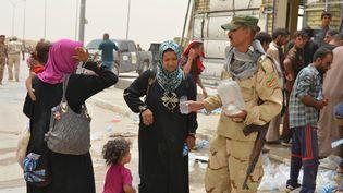 Un soldat irakien aide les civils qui fuient Falloujah (Irak, le 18 juin 2016 (OSAMAH WAHEEB / REUTERS)