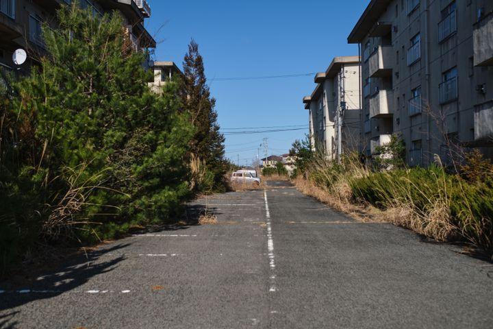 Des immeubles d'habitation abandonnés à l'intérieur de la zone réglementée de Fukushima, le 3 mars 2021 à Namie. (NICOLAS DATICHE / SIPA)