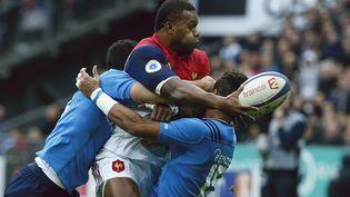 L'ailier du XV de France, Virimi Vakatawa résiste à la charge de deux joueurs italiens, lors du match France-Italie, le 6 février 2016, au Stade de France. (THOMAS SAMSON / AFP)