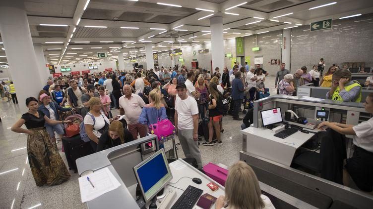 Des clients de Thomas Cook attendent dans l'aéropot de Palma de Majorque (Espagne), le 23 septembre 2019. (JAIME REINA / AFP)