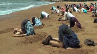Des manifestants mettent la tête dans le sable, le21 septembre 2014sur la plage de Townsville (Australie), pour dénoncerla politique de l'autruche face au réchauffement climatique. (CRANKY CURLEW / VIMEO)