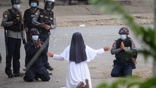 Sœur Ann Roza Nu Thawng à genoux devant les forces de l'ordre, à Myitkyina, dans le nord dela Birmanie. (HANDOUT / MYITKYINA NEWS JOURNAL / AFP)