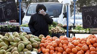 Un homme portant un masque de protection fait ses courses sur le marché de Crépy-en-Valois (Oise) le 1er mars 2020, avant son évacuation par la police en raison de l'interdiction liée à l'apparition du nouveau coronavirus. (FRANCOIS LO PRESTI / AFP)