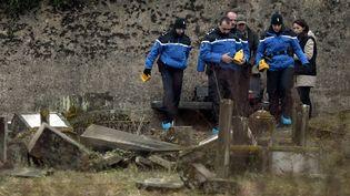 Des gendarmes enquêtent dans le cimetière juif de Sarre-Union (Bas-Rhin), le 16 février 2015, deux jours après la découverte de la profanation de 250 tombes. (FREDERICK FLORIN / AFP)