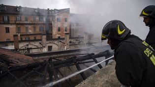 Des pompiers éteignent un incendie àl'Ecurie royale, à Turin (Italie), le 21 octobre 2019. (MARCO BERTORELLO / AFP)
